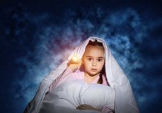 Frightened girl with flashlight under blanket. Frightened girl with flashlight hiding under blanket. Scared kid lying in his bed at home. Fear of the dark stock images