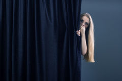 Frightened girl. Hiding behind a curtain Stock Photo