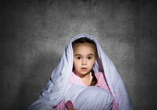 Frightened girl hiding under blanket. Scared kid lying in his bed at home. Fear of the dark. Beautiful little girl can not sleep at night. Portrait of child in royalty free stock image