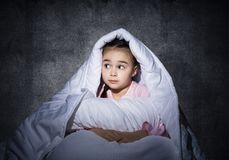 Frightened girl hiding under blanket. Scared kid lying in his bed at home. Fear of the dark. Beautiful little girl can not sleep at night. Portrait of child in royalty free stock photos