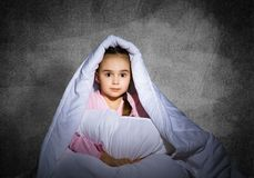 Frightened girl hiding under blanket. Scared kid lying in his bed at home. Fear of the dark. Beautiful little girl can not sleep at night. Portrait of child in royalty free stock images