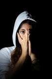 Frightened girl in hood on black background Stock Photo
