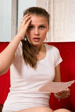 Frightened girl reading a medicine instruction Stock Images