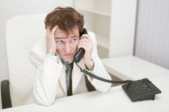 Frightened guy speaks by phone at office Royalty Free Stock Photography