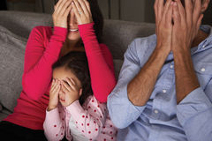 Frightened Hispanic Family Sitting On Sofa And Watching TV Royalty Free Stock Photos