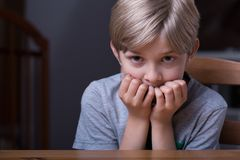 Frightened kid sitting at table Stock Photo