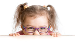 Frightened kid in spectacles looking from under. Table royalty free stock image