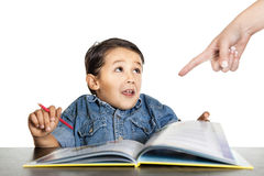 Frightened little boy looks at a finger that points to homework Stock Image