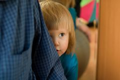 Frightened little girl. Is hiding behind father's back Royalty Free Stock Photos