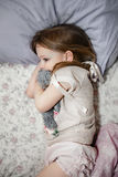 The frightened little girl in bed with her teddy bear Stock Photo