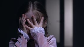 Frightened little girl closing face with palms, afraid of ghosts phobia concept. Stock footage stock footage