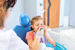 Frightened little girl. In the dental chair Stock Photos