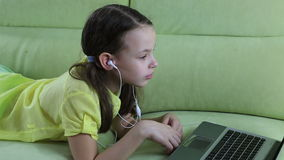 Frightened little girl looks terrible video on laptop. stock footage