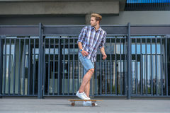 Frightened male skater running from something. Funky young man is escaping from someone on skateboard. He is looking back with fear Royalty Free Stock Image