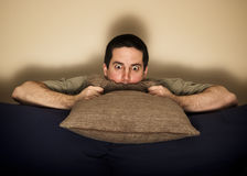 Frightened man hides behind a pillow Royalty Free Stock Photo