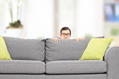 Frightened man hiding behind a sofa. Isolated on white background Stock Photos