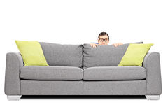 Frightened man hiding behind a sofa. Isolated on white background Stock Image