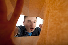 Frightened man looking to paper bag Stock Photos