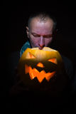 Frightened man looks inside a glowing pumpkin Stock Photography