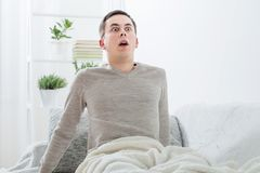 Frightened man on the sofa Royalty Free Stock Images