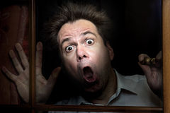Frightened man. Stands behind a window Royalty Free Stock Photos