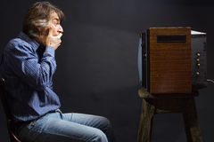The frightened man watching TV. Stock Photo