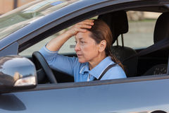 Frightened mature woman in   car. Stock Images