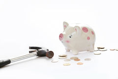 Frightened piggy bank is being to smashed on white background Royalty Free Stock Photo