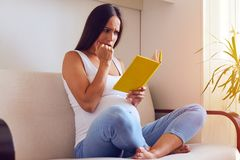 Frightened pregnant woman reading book. Side view of frightened pregnant woman reading book sitting on sofa at home Stock Image