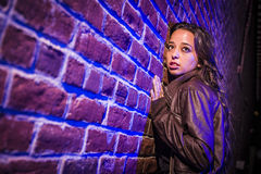 Frightened Pretty Young Woman Against Brick Wall at Night Royalty Free Stock Photography