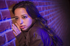 Frightened Pretty Young Woman Against Brick Wall at Night Stock Photo