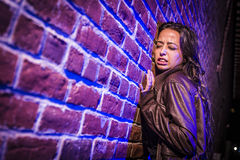 Frightened Pretty Young Woman Against Brick Wall at Night Stock Images