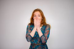 Frightened red-haired beautiful young woman. Scared Frightened red-haired beautiful young woman with her eyes open her eyes on white background Royalty Free Stock Photography