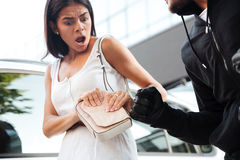 Frightened shocked young woman being robbed by thief outdoors Stock Photo