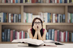 Frightened student in library. Portrait of frightened female college student with textbooks biting her nails. shot in the library Stock Images
