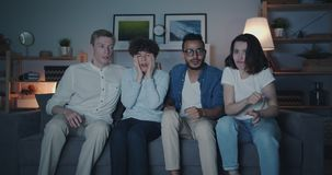 Frightened students watching thriller on TV with scared faces at night at home stock video footage