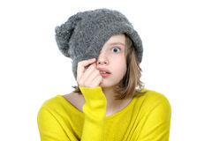 Frightened teen girl covers her face with a cap. Frightened teen girl covers her face with a cap on a white background royalty free stock images