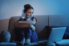 Frightened teenage girl with laptop on sofa. Danger of internet. Frightened teenage girl with laptop on sofa in dark room. Danger of internet stock image