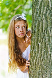 Frightened teenage peeping from. Beautiful frightened teenage peeping from behind tree, against green of summer park royalty free stock photography
