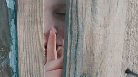 Frightened teenager boy with blue eyes peeks through a gap between a fence or a doorway and shows a finger of a sign of. A frightened teenager boy with blue eyes stock footage