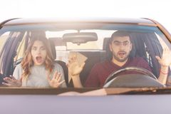 Frightened terrified couple in car can`t control speed, drive fast, afraid of being safe, scream with shock as have accident, bein. G very emotional. People Royalty Free Stock Photo