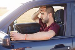 Frightened terrified dark haired unshaved man, stops his car on side of road, drinks tea, sees with shock through windshield at. Accident, being very emotional stock image