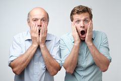 Frightened two men have scared expressions, look nervously, isolated over white background. Emotive mature father and son have shocked faces stock photo