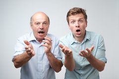 Frightened two men have scared expressions, look nervously, isolated over white background. Emotive mature father and son have shocked faces royalty free stock image