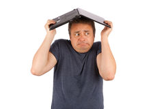 Frightened user hiding under a laptop Stock Image