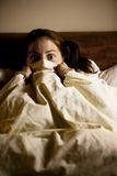 Frightened Woman in Bed Royalty Free Stock Photos