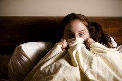 Frightened Woman in Bed Stock Photography