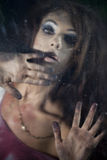 Frightened woman behind the glass Royalty Free Stock Photos