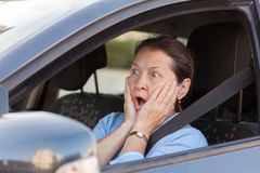 Frightened woman in black car. Portrait of frightened senior woman in black car stock image