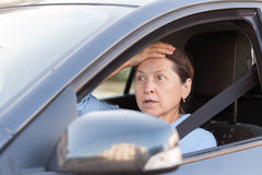 Frightened woman in car. Portrait of frightened senior woman in black car royalty free stock image